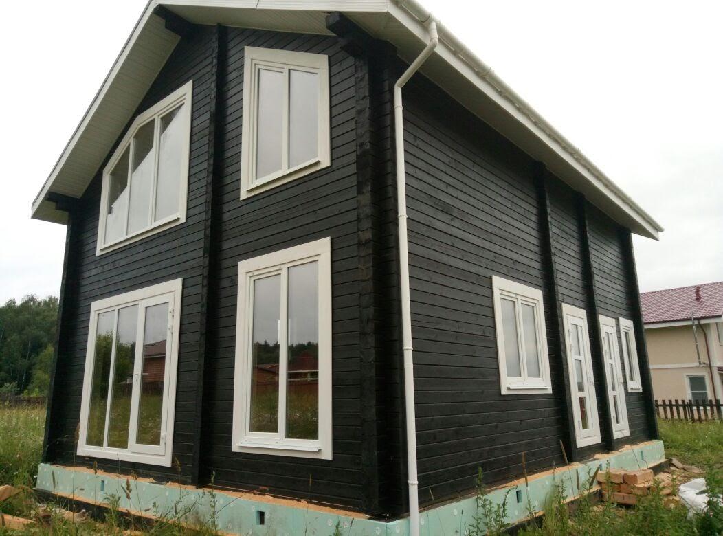 Черный дом с белыми наличниками